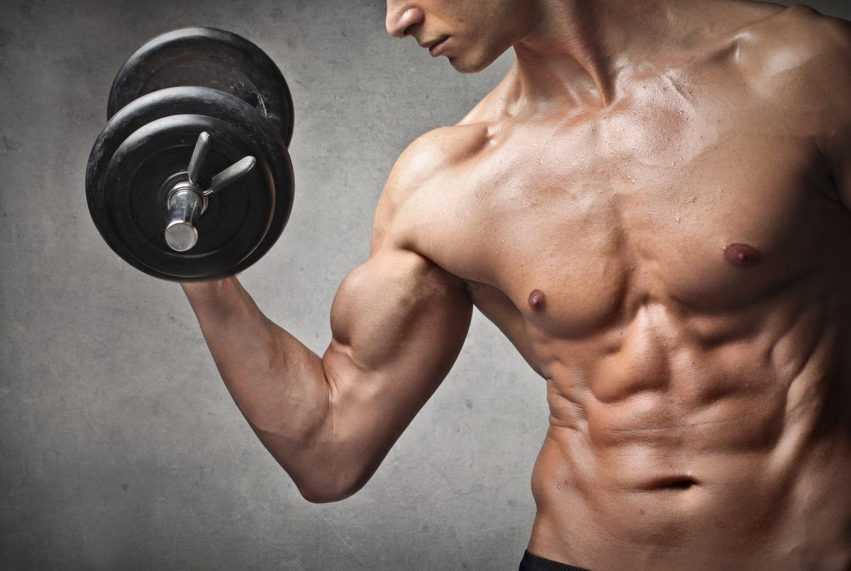 Man lifting heavy Dumbbells to increase Muscular Mass.